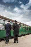 Prepare to depart. HORSTED KEYNES, UK - MARCH 19, 2016: Ticket inspectors stand on platform by departing train on The Bluebell Line Stock Photos