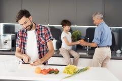Prepare una ensalada para la acción de gracias con la familia entera Un hombre, su padre y el hijo preparan una ensalada en la co Imagen de archivo