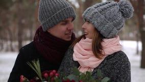 Prepare viene a la novia, abrazos y la besa de la parte posterior en bosque del pino del invierno de la nieve durante las nevadas almacen de video