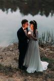 Prepare y su nueva esposa encantadora con la vela ardiente en la orilla del lago del bosque en la tarde fotografía de archivo