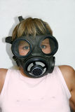 Prepared. Young blonde woman in a gas mask royalty free stock photo