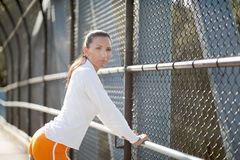 Prepared for anything. Confident female athlete leaning against a railing, looking at the camera Royalty Free Stock Image
