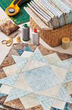 Prepared blocks for sewing quilt, stack of fabrics, sew accessories Stock Photo