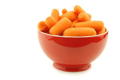 Prepared carrots in a red ceramic bowl. On a white background Royalty Free Stock Image