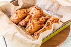 Prepared chicken drumsticks in pan Stock Images