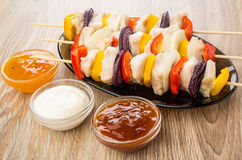 Prepared chicken shashlik in brown dish, bowls with sauces on wo Stock Images