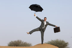 Prepared for a climate change. Suited buisnessman in a desert with an umbrella Royalty Free Stock Photo