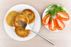 Prepared cutlets in plate with dill and tomatoes on table Stock Images