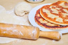 Ready fried wheat pitas and raw yeast dough. Prepared fried flour tortillas on a plate and raw yeast dough Stock Images