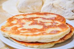 Ready fried wheat pitas and raw yeast dough. Prepared fried flour tortillas on a plate and raw yeast dough Stock Photos