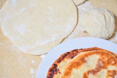 Ready fried wheat pitas and raw yeast dough. Prepared fried flour tortillas on a plate and raw yeast dough Royalty Free Stock Images