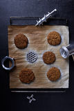 Prepared ground beef patties or cutlets on a baking tray with steal grinder parts, dark background. Royalty Free Stock Photos
