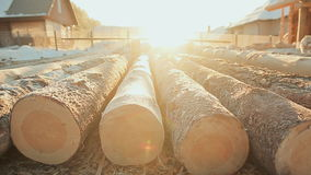 Prepared logs lie on the construction of a wooden house. Shining frosty sun. Winter construction site. Canadian angle stock video footage