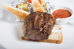 Prepared mignon steak. Served with croutons and sauce royalty free stock photography