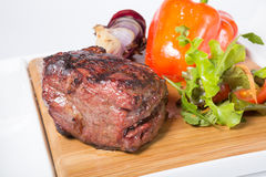 Prepared mignon steak. With vegetables garnish on a wooden board royalty free stock image