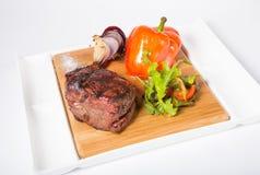 Prepared mignon steak. With vegetables garnish on a wooden board stock photo