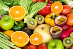 Prepared orange slice with group of ripe fruits and vegetables Stock Images