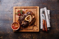 Prepared Osso buco Veal shank. With tomatoes on serving board on wooden background Stock Image