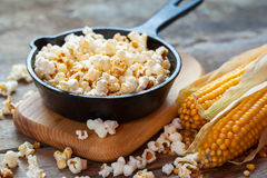 Prepared popcorn in frying pan, corn seeds and corncobs Stock Images