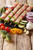 Prepared raw marinated pork shish kebab with pepper on skewers c. Lose-up and ingredients, vegetables, spices, herbs on the table. vertical royalty free stock photography