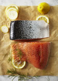 Prepared raw salmon fillets on parchment paper. Two raw salmon fillets with silver skin laying on parchment paper with lemon slices and fresh dill Royalty Free Stock Photo