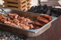 Prepared shashlik and sausages Stock Photos