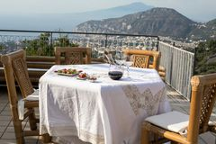 Prepared for supper table on the terrace overlooking the Bay of Naples and Vesuvius. Sorrento. Italy royalty free stock photo