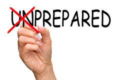 Prepared. Text 'unprepared' in black uppercase letters on white background with letters 'un' crossed out in red with a pen held in a woman's hand Stock Image