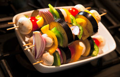 Prepared and uncooked vegetable kebabs. Vegetable kebabs of mushroom, aubergine, red onion, baby tomato, and green and yellow pepper. Photo has short depth of Royalty Free Stock Photos