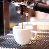 Prepares espresso in his coffee shop; close-up Stock Photo