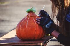 Prepares jack-o-lantern for Halloween. Decoration for party. All saints day. Prepares jack-o-lantern for Halloween. Decoration for party. The female at a table Stock Photography