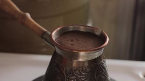 Prepares traditional turkish coffee in copper pot over stove.  stock video