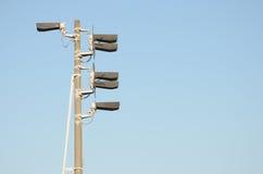 Prepari la luce del semaforo con sei lampade ad un'alta colonna concreta grigia contro cielo blu Immagine Stock