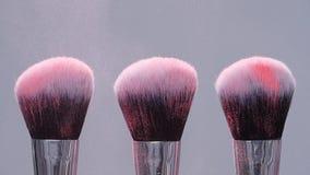 Prepari la spazzola con polvere rosa spruzza l'esplosione su fondo grigio su movimento lento video d archivio