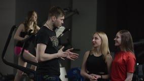Prepari viene ad accogliere alle ragazze adorabili in nuova palestra e chiedono notizie su loro con la ragazza impegnata in simul stock footage