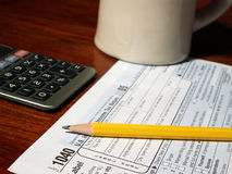 Preparing 1040 tax form. Tax form, pencil, calculator and mug stock images