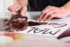 Preparing adhesive shop window sign Stock Image