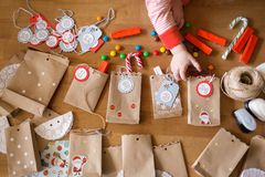 Preparing the advent calendar. bags and sweets on the table. little baby arms to reach for the candy royalty free stock image