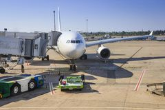 Preparing aircraft for flight. Servicing of aircraft at the airport. The plane in the terminal of the airport on a clear salty day. Loading luggage and Royalty Free Stock Photography