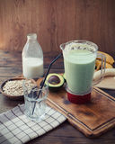 Preparing avocado smoothie. On wooden table Royalty Free Stock Image