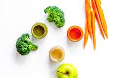 Preparing baby food. Broccoli, pumpkin, apple puree on white background top view copyspace Stock Photo