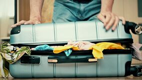 A man trying to pack overfilled suitcase