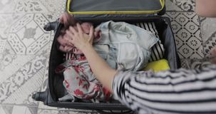 Top view packing suitcase girls planning road trip. Preparing bag for travel. Young woman packing and standing her bare knees on overfilled suitcase and closes a stock video footage
