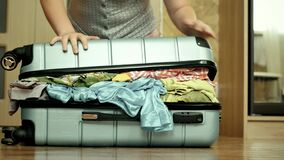 Young woman trying to pack overfilled suitcase