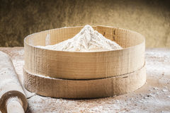 Preparing bakery products with flour. White flour on a sieve and a paddle near it ready to be prepared for bread and bakery products Stock Image