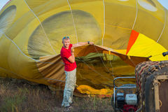 Preparing the baloon. hot air. big baloon. flight. come fly with me. in the field. yellow baloon. summer fun. a men holding baloo. Preparing the baloon. hot air Stock Photo