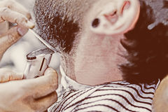 Preparing a beard. Detail of a beard is being shaved with a hair clipper - focus on the comb royalty free stock photography