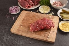 Preparing beef roulades, fresh raw meat stuffed with mustard, on. Ions, pickled cucumber and bacon on a wooden cutting board, dark slate kitchen countertop Stock Photos