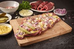 Preparing beef roulades on a wooden cutting board, fresh raw mea. T with mustard, onions, pickled cucumber and bacon, dark kitchen countertop, selected focus Stock Photos