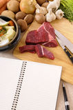 Preparing beef steak casserole or stew with ingredients and herbs on kitchen wood cutting board with cookbook or recipe book Royalty Free Stock Image